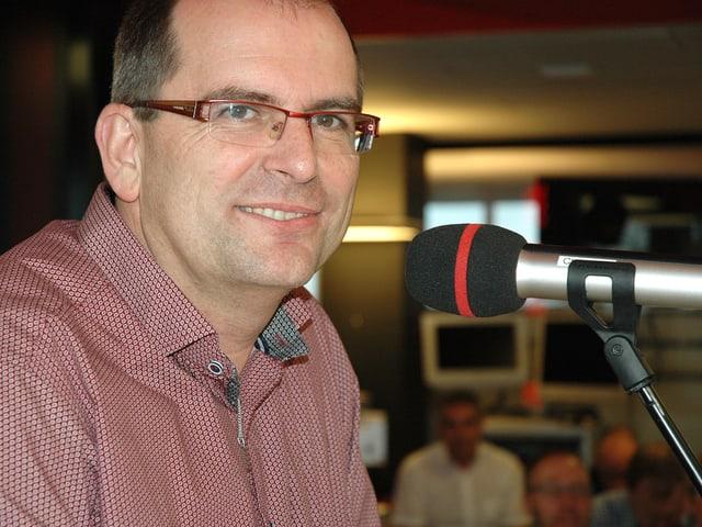 Mann mit Brille am Mikrofon.