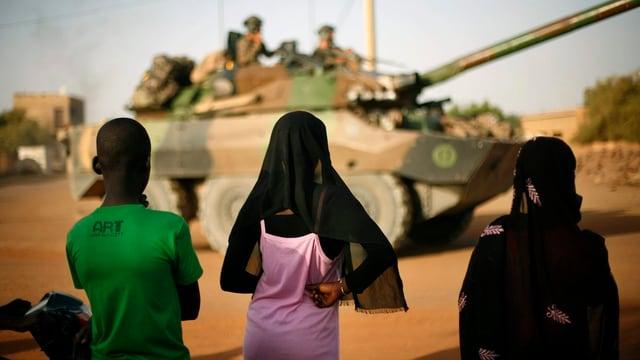 Kinder und im Hintergrund ein Panzer.