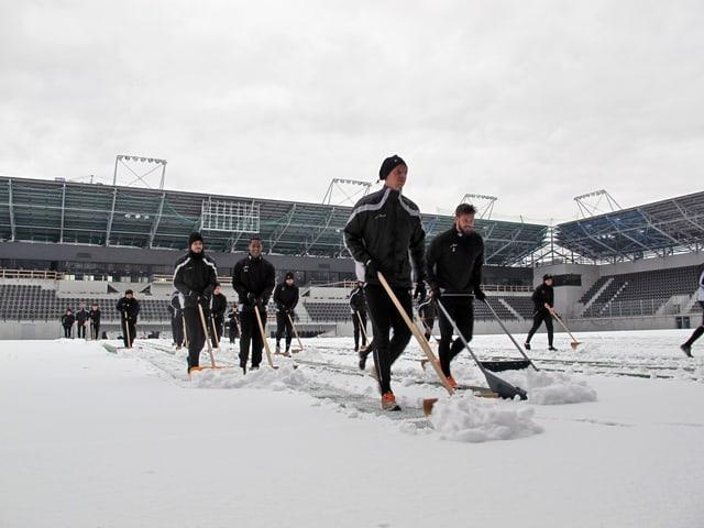 Männer in Trainingsanzügen und Mützen schieben mit grossen Schaufeln den Schnee von einer Wiese.
