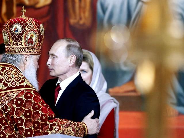 Präsident Putin wird von einem orthodoxen Patriarchen umarmt.