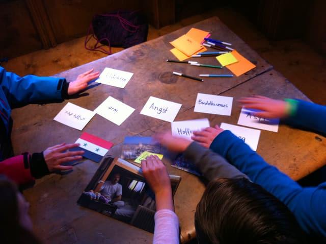 Auf einem Tisch liegen Karten mit Stichworten wie «Angst» oder «» beschriftet. Hände mischen die Karten durcheinander.