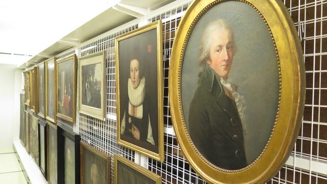 Reihe von alten Portraitgemälden an einer Gitterwand.