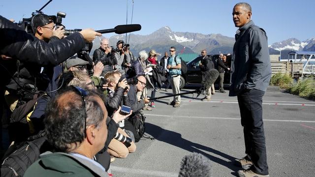 Obama an einem Hafen, links jede Menge Journalisten mit Mikrofonen, im Hintergrund Berge mit Schnee.
