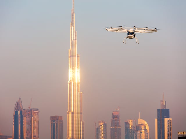 Volocopter fliegt vor einem Hochhaus in Dubai vorbei.