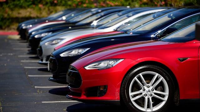 Autos des Modells Tesla S in einer Reihe auf deinem Parkplatz.