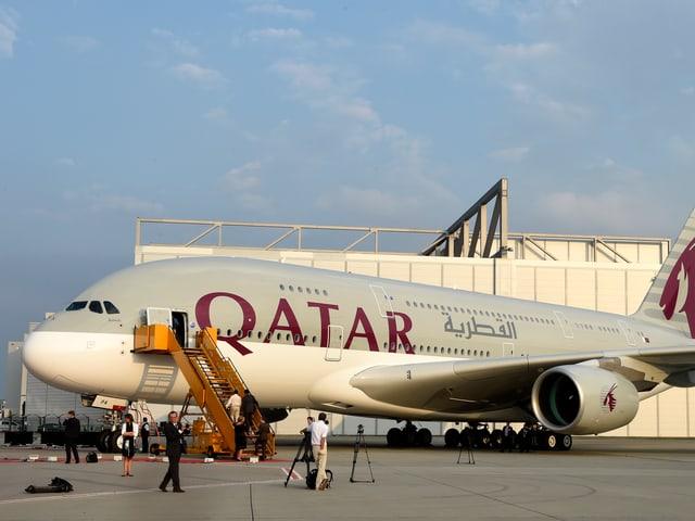 A380 geparkt auf dem Flugfeld, Menschen stehen darum herum.
