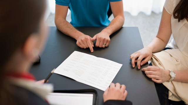 Zwei Bankkunden und eine Beraterin besprechen eine Kontoeröffnung