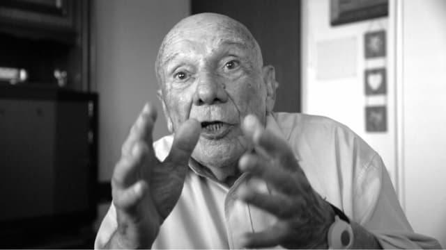 ein Mann gestikuliert wild in die Kamera (schwarz-weiss Aufnahme)