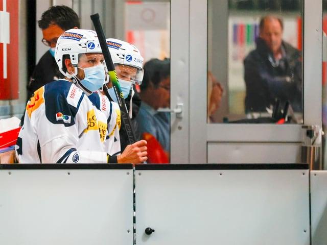 Eishockey-Spieler auf der Strafbank mit Maske