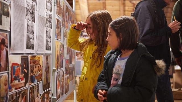 Zwei Mädchen vor einer Zeitungswand