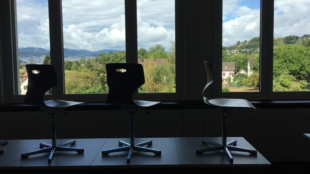 Der Blick auf einen Tisch, auf dem drei Stühle stehen. Dahinter eine grüne Landschaft.