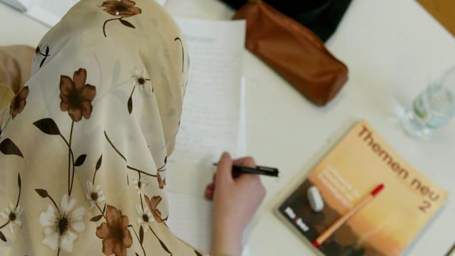 Ein muslimisches Mädchen mit Kopftuch beim Schreiben.
