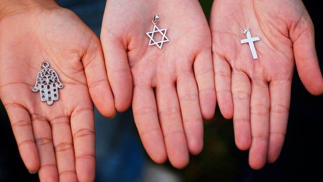 Hände halten Symbole für Islam, Judentum und Christentum in den Händen.