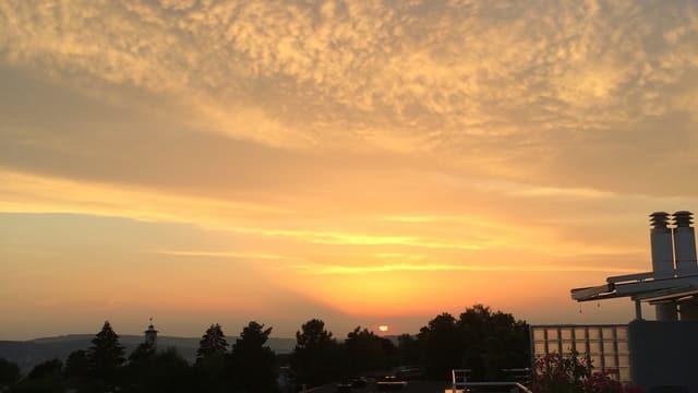 Untergehende Sonne zwischen rotbeschienen Wolken.