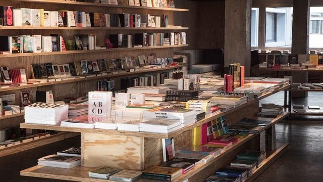 Blick in einen Bücherladen mit Tisch im Vorgrund und Gestell im Hintergrund