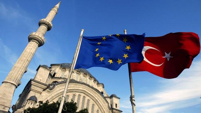 Die Flaggen der EU und der Türkei vor einer Moschee.