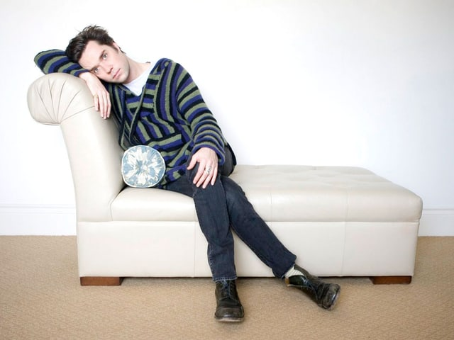 Rufus Wainwright sitzt auf einem hellen Sofa.