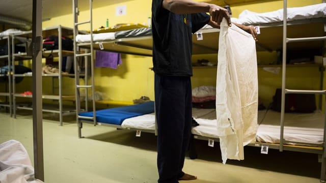Mann mit dunkler Haut faltet ein Bettlaken in einer Zivilschutzanlage