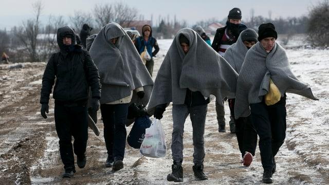 Flüchtlinge mit Wolldecken um den Kopf