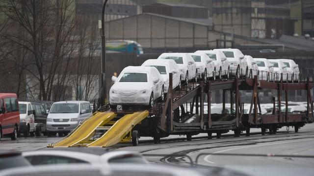 Autos novs protegids cun ina cuverta sin in char da tren.