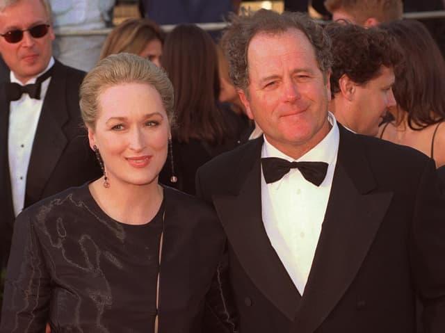 Links eine schwarz gekleidete Frau, rechts ein Mann im Anzug.