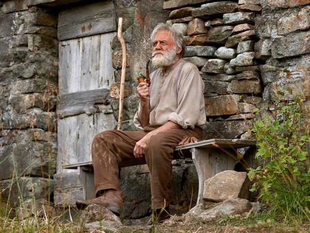 Bruno Ganz raucht vor seiner Alphütte mit grimmigem Blick Pfeife.