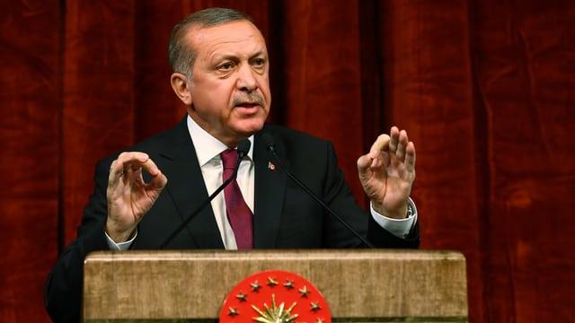 Erdogan am Rednerpult mit bestimmter Handgestik und Bilck.