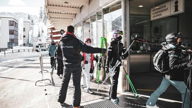 turists da skis cun mascrinas tar la staziun a val da las pendicularas d'Arosa