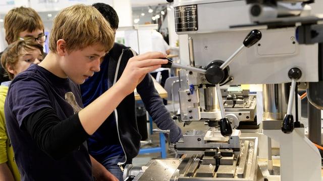 Ein Jugendlicher steht vor einer Maschine, die an der Seite ein dreiteiliges Rad hat. Er dreht mit seiner rechten Hand daran.