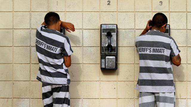 Zwei Männer in gestreifter Kleidung mit dem Rücken zur Kamera am Telefonieren.