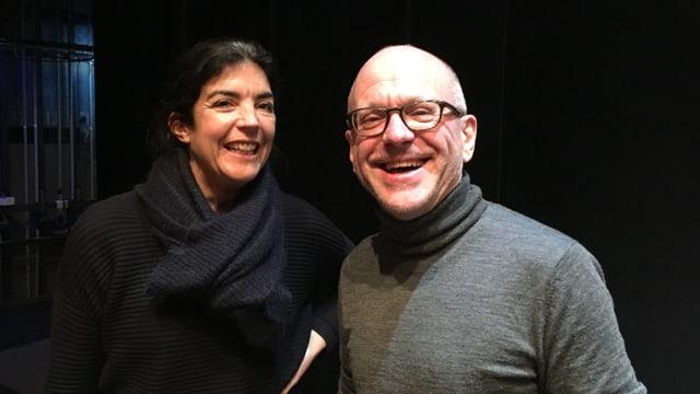 Eine Frau und ein Mann lachen neben einer Theaterbühne in die Kamera.