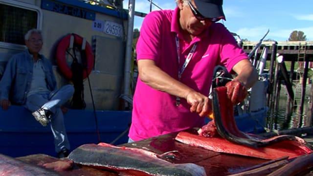 Ein Mann schneidet filetiert einen Lachs am Hafen.