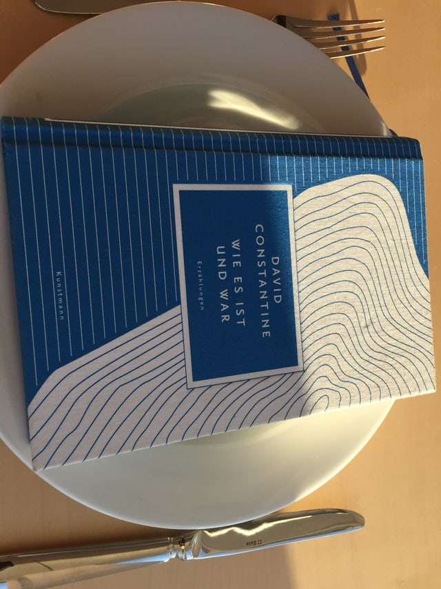 Das Buch «Wie es ist und war» von David Constantine liegt auf einem weissen Teller