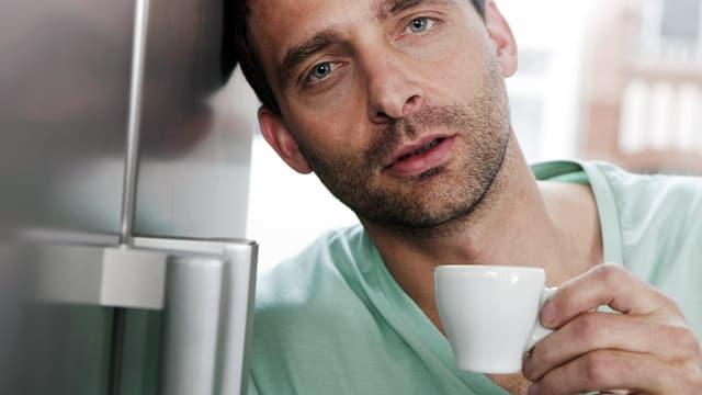 Mann mit müdem Gesicht und einer Espressotasse in der Hand lehnt an einen Kühlschrank