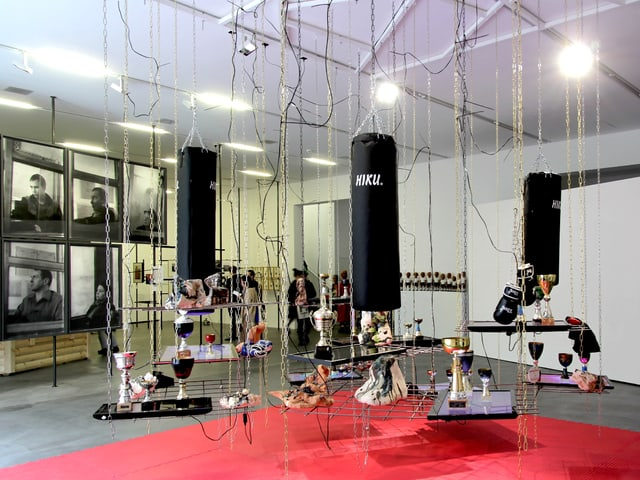 Ein Raum in dem von Seilen Bretter hängen, auf diesen liegen Objekte: Trophäen, Boxhandschuhe.