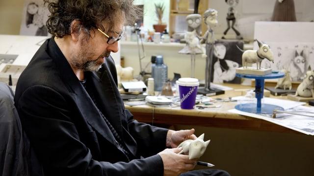 Tim Burton hält eine Figur aus dem Film «Frankenweenie» in den Händen, auf dem Pult stehen weitere Figuren aus dem Film.