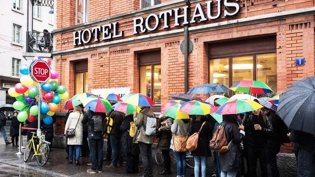 Menschen stehen mit bunten Regenschirmen Schlange.