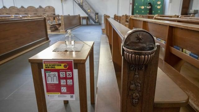 Desinfektionsmittel steht neben dem leeren Weihwasserbecken einer Kirche.