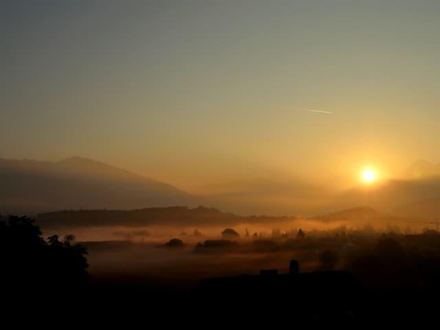 Nebelschwaden in den tiefsten Lagen, Sonne erscheint gerade hinter einem Berg.