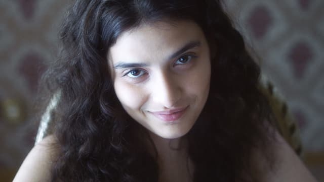 Eine junge Frau lächelt in die Kamera.