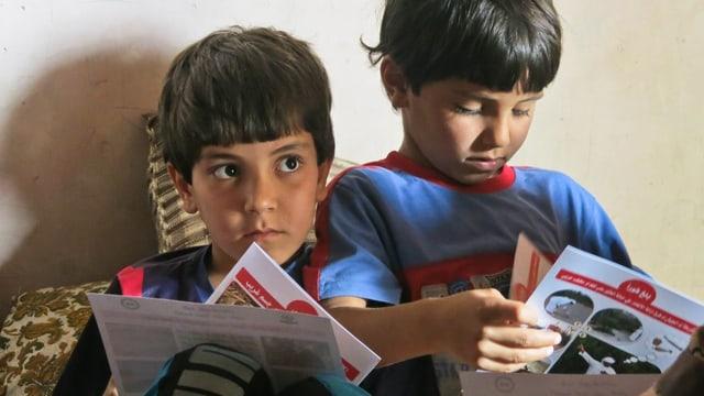 Zwei Brüder schauen sich Prospekte an, die Handicap International bei einer Aufklärungsveranstaltung abgegeben hat.