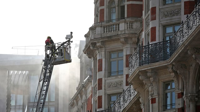 Feuerwehrmann auf Feuerleiter vor dem Hotel