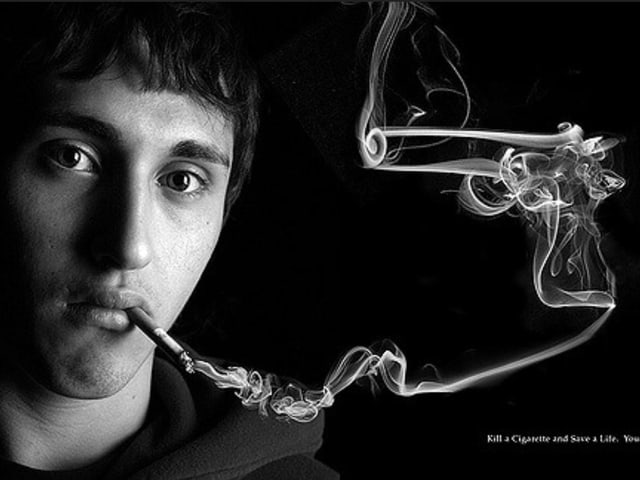 Rauchender Mann, neben seinem Gesicht eine Pistole aus Rauch.