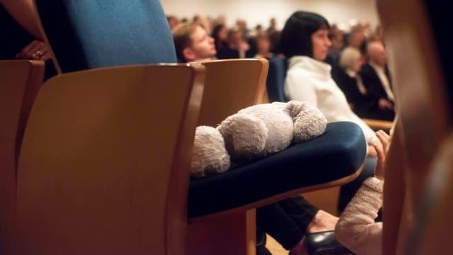 Ein Teddy liegt auf einem Stuhl in einem Konzertsaal.