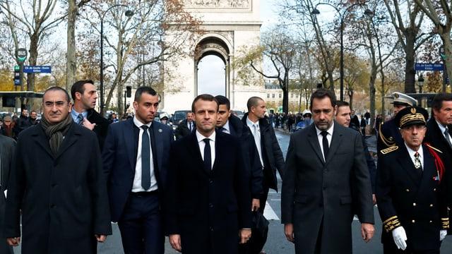 Macron und weitere Männer auf den Champs Elysées, im Hintergrund der Arc de Triopmphe.