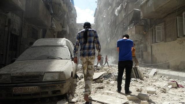 Dus umens avant ina auto destruì ad Aleppo en Siria.