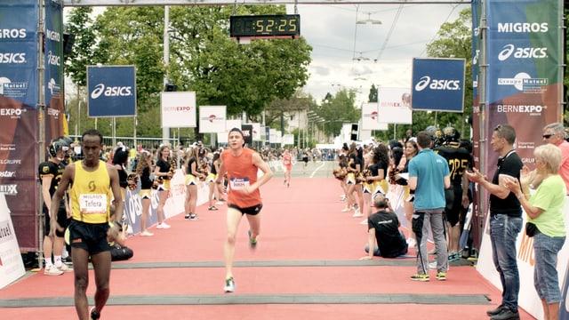Zwei Marathonläufer überqueren die Ziellinie des Laufs.