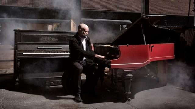 Ein Mann im Frack an einem roten Flügel auf einem rauchenden Dachboden.