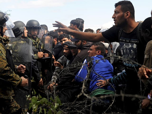 Polizisten und Flüchtlinge stehen sich gegenüber, getrennt durch einen Stacheldraht