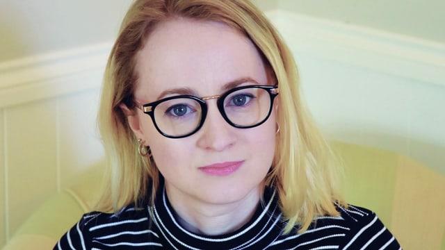 Eine blonde Frau mit Brille, Porträt.